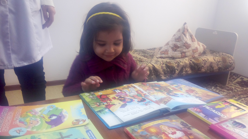 A girl is playing in a Children Room established inside polling station of Bukhara while her mother is casting her vote at ease